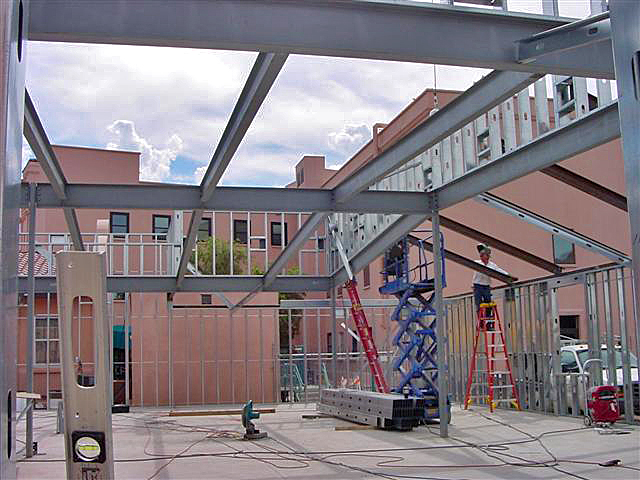 A steel frame for a commercial building. A man on a scissor lift installing beams