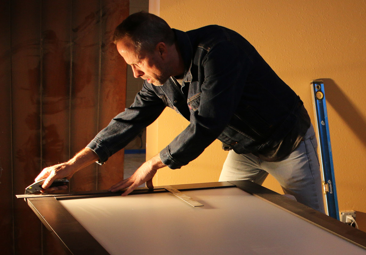 Vincent Alvord adjusting a sliding glass door